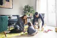 Parents and son playing with toys at home - CAVF44479