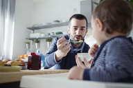 Father feeding breakfast to son sitting in high chair at home - CAVF44482