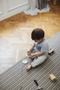 High angle view of baby boy playing with toy teacup and saucer on rug at home - CAVF44542