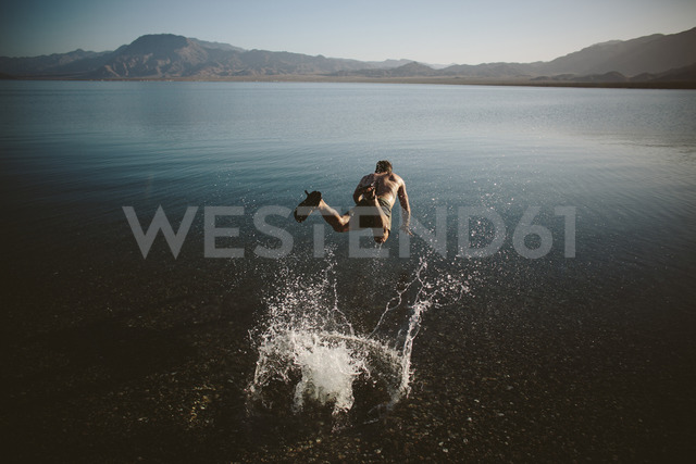 High angle view of shirtless man jumping into lake against mountains - CAVF44569