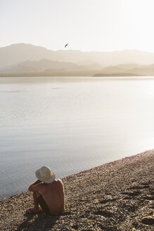 High angle view of shirtless man sitting at lakeshore against mountains and clear sky during sunny day - CAVF44572