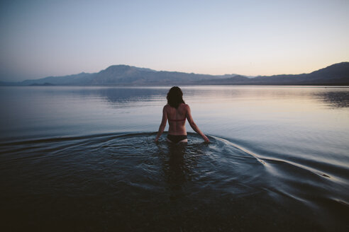 Rear view of woman wearing bikini while standing in lake against clear sky during dusk - CAVF44575
