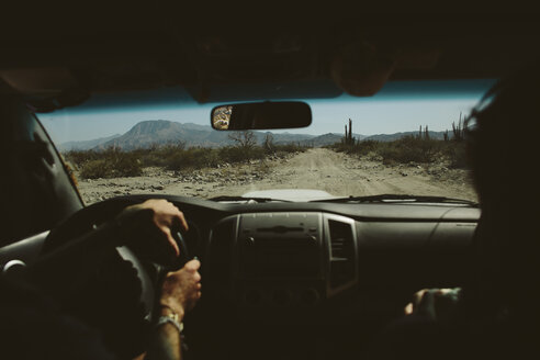 Cropped image of friends in off-road vehicle on dirt road against mountains - CAVF44578