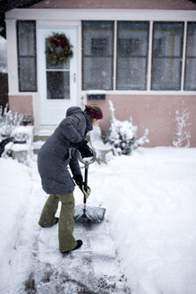 Woman shoveling snow outside house - CAVF44644