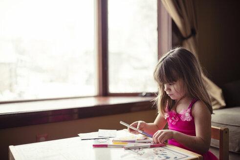 Girl holding felt tip pen at table in living room - CAVF44653