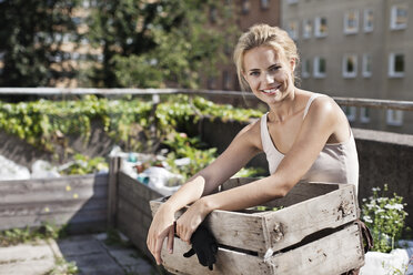 Portrait of happy young woman with wooden crate sitting at urban garden - MASF06064