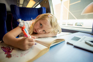 Portrait of girl drawing pictures while sitting on train's seat - MASF06076