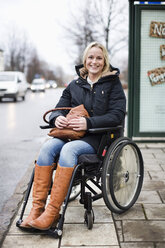 Portrait of happy disabled woman in wheelchair smiling outdoors - MASF06097