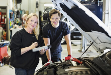 Portrait of happy mid adult female mechanic holding digital tablet standing with coworker by open car hood - MASF06118