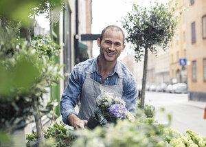 Portrait of happy male florist working outside flower shop - MASF06124