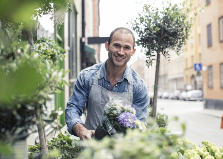Portrait of happy male florist working outside flower shop - MASF06124