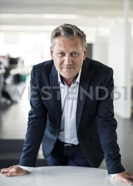 Portrait of mature businessman leaning on desk in office - MASF06142 - Maskot ./Westend61