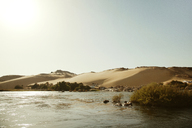 Scenic view of Nile river by sand dune against clear sky at Aswan on sunny day - CAVF44695