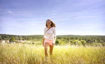 Woman walking on grassy field against sky - CAVF44875