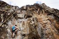 Low angle view of man rock climbing - CAVF44911