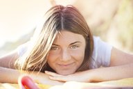 Portrait of woman lying at beach - CAVF45001