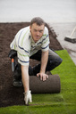 Portrait of a mid adult man rolling new grass turf in lawn - MASF06160