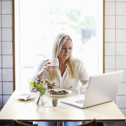 Mid adult woman using laptop while holding glass of water at restaurant table - MASF06169