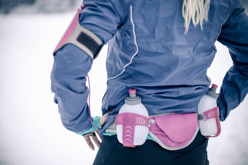 Midsection of woman wearing water bottle belt in winter - MASF06181