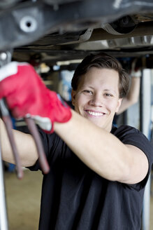 Portrait of confident young male mechanic working underneath car at workshop - MASF06184