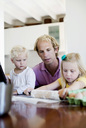 Man looking at little daughter rolling dough on table in kitchen - MASF06205