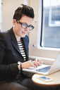 Mid adult businesswoman using laptop in train - MASF06229