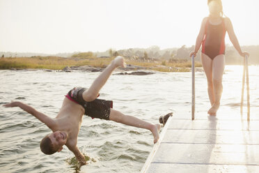 Little boy jumping in water with sister standing on pier - MASF06262