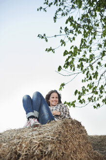 Happy young woman sitting on haystack - MASF06289