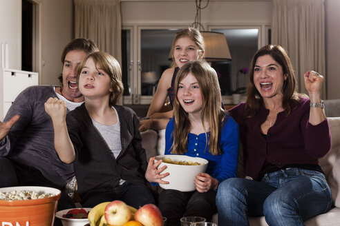 Happy family cheering while watching TV in living room - MASF06382