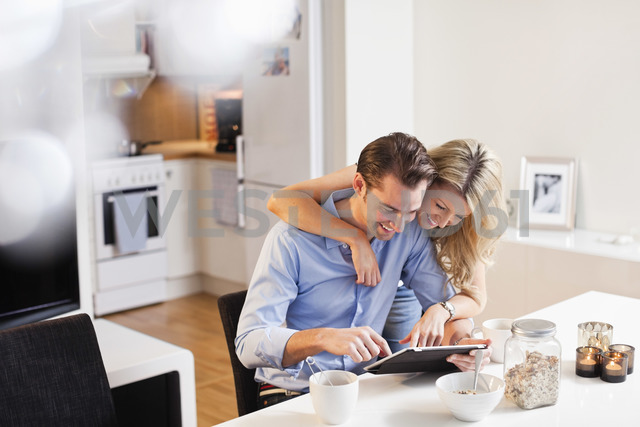 Happy couple using digital tablet at breakfast table - MASF06388