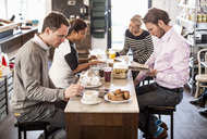 Businessmen and businesswomen having breakfast together in office restaurant - MASF06412