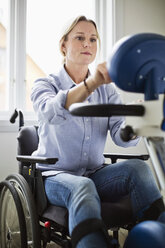 Disabled woman in wheelchair using motomed bike - MASF06442