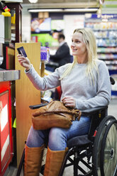 Disabled woman in wheelchair paying through credit card at supermarket - MASF06445