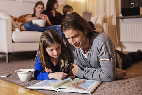 Father and daughter reading map on floor with family sitting on sofa in living room - MASF06454