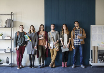Portrait of friends standing against wall in classroom - CAVF45008