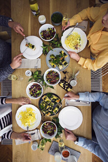 Overhead view of friends eating lunch while sitting at dinning table in party - CAVF45119