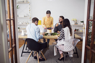 Happy friends enjoying party at dinning table in home - CAVF45125