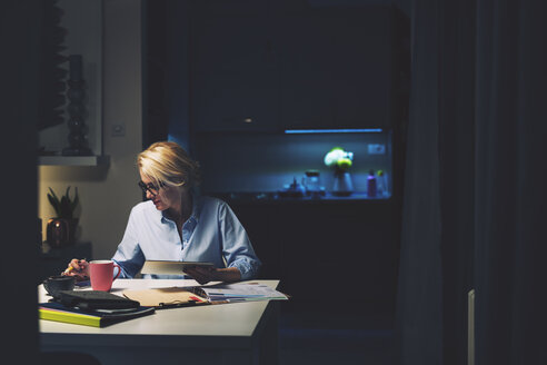 Businesswoman using technologies while sitting at desk in home office - CAVF45131