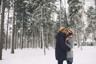 Romantic couple kissing while standing on snow covered field in forest - CAVF45224