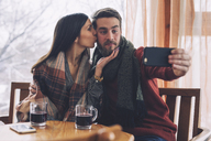 Woman kissing while boyfriend taking selfie at table in cafe - CAVF45227