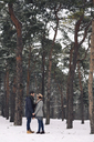 Happy couple looking at each other while standing on snow covered field in forest - CAVF45233