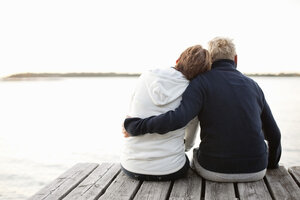 Rear view of mature couple sitting on pier looking at lake - MASF06498