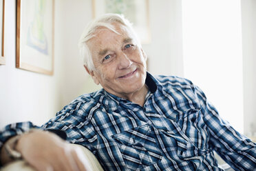 Portrait of smiling elderly man sitting in living room - MASF06513