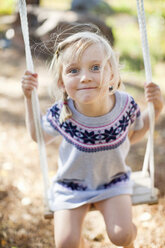 Portrait of small girl on rope swing in back yard - MASF06519