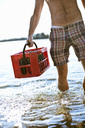 Midsection of mature man carrying drinks crate in lake water - MASF06537