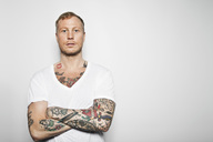 Portrait of a tattooed man with arms crossed standing against grey background - MASF06549
