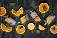 Homemade detox popsicles with blueberries, orange slices and mint leaves on black wood - RTBF01167