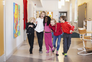 Happy children walking in school corridor - MASF06564