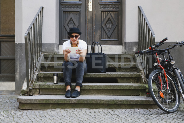 Woman sitting on stairs with coffee to go using tablet - RTBF01171