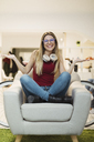 Happy casual young woman sitting in armchair in coworking space - OCAF00217